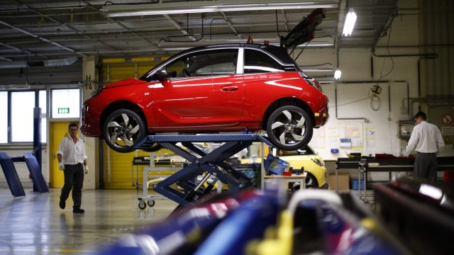 Workers are pictured next to an Opel Adam car during the start of the car production in Eisenach