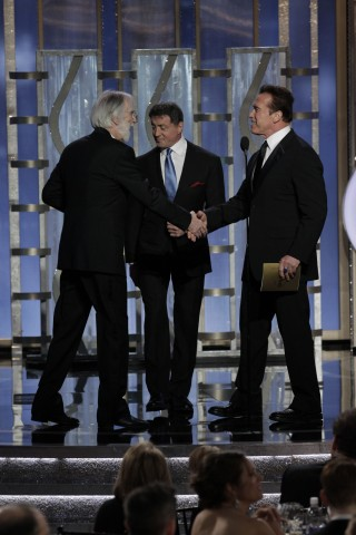 Presenters Sylvester Stallone and Arnold Schwarzenegger greet Michael Hanekeat the Golden Globe Awards in Beverly Hills