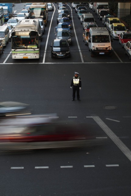 A policeman directs the traffic at a busy street of downtown Shanghai