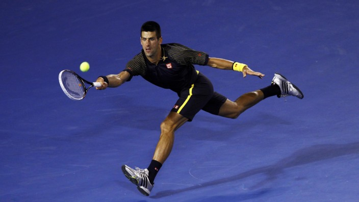 Novak Djokovic of Serbia hits a return to Andy Murray of Britain during their men's singles final match at the Australian Open tennis tournament in Melbourne