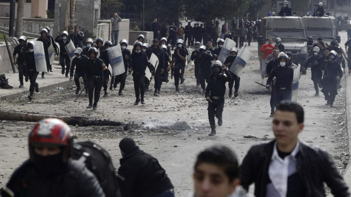 Riot police run towards protesters opposing Egyptian President Mursi during clashes, along Qasr Al Nil bridge, which leads to Tahrir Square in Cairo
