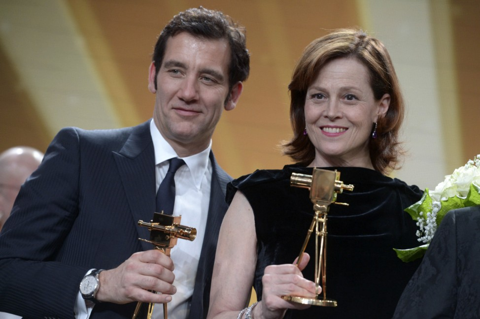 Britsh actor Clive Owen and U.S. actress Sigourney Weaver hold their trophies during 48th Golden Camera award ceremony in Berlin
