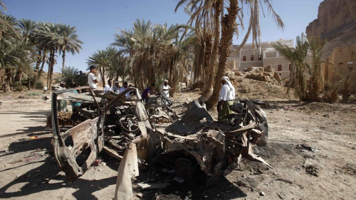 People gather near the wreckage of a car destroyed by a U.S. drone air strike that targeted suspected al Qaeda militants in August 2012, in al-Qatn