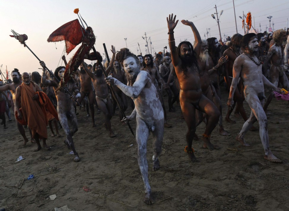 Sadhus or Hindu holy men gesture and shout after taking a dip during the second 'Shahi Snan' of the ongoing 'Kumbh Mela' in Allahabad