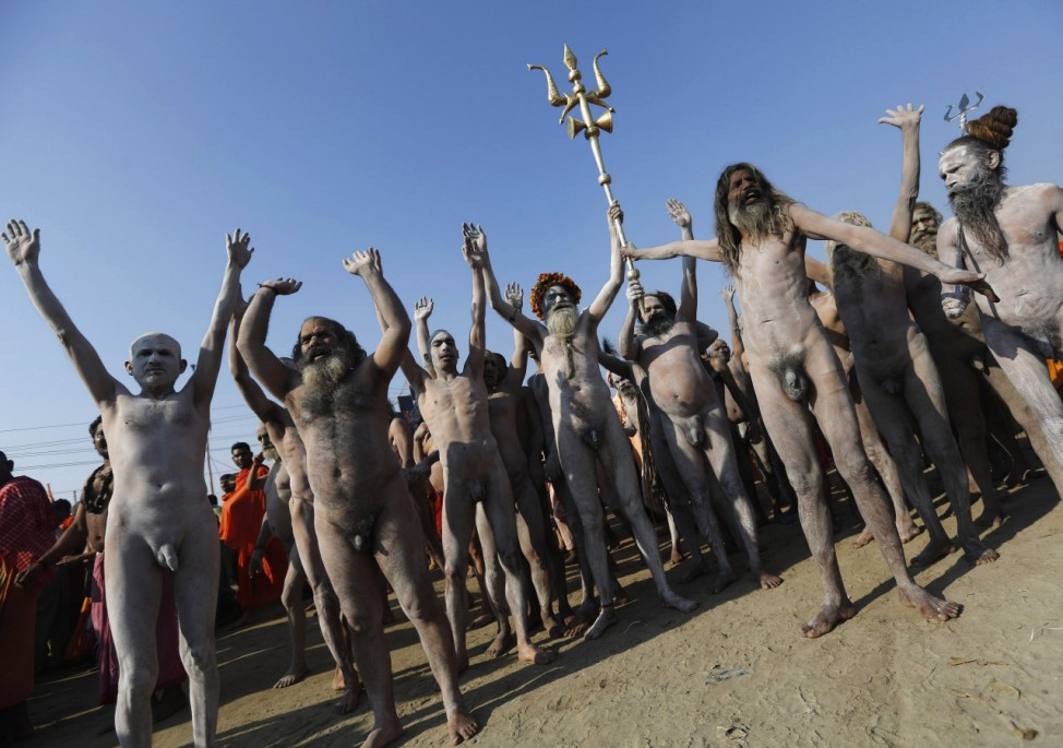 Sadhu or Hindu holy men gesture as one of them holds a 'trishul' or trident-shaped weapon after taking a dip during the 'Kumbh Mela' in Allahabad
