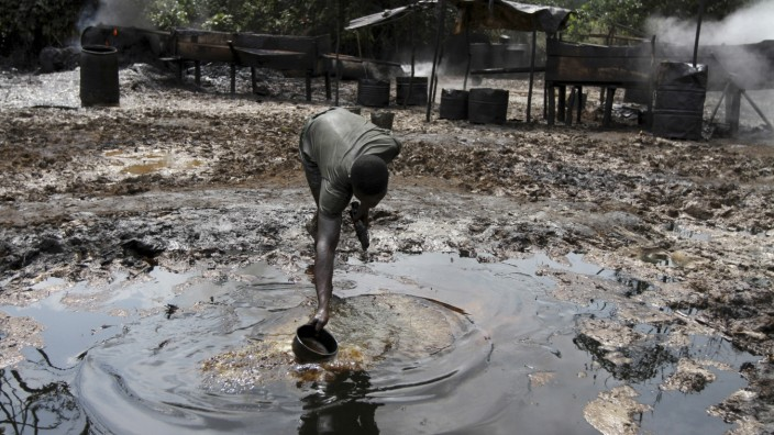 File photo shows a man collecting polluted water at an illegal oil refinery site near river Nun in Bayelsa