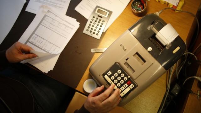 Peter Breiter, CEO of Raiffeisen Gammesfeld eG bank, works with an old adding-machine at the bank in Gammesfeld, Baden-Wuerttemberg
