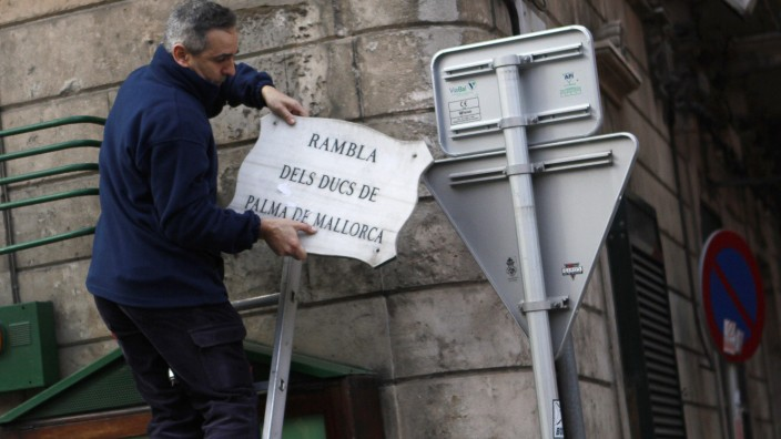 A worker removes a street placard bearing the title of Spain's Infanta Cristina and her husband Inaki Urdangarin in Palma de Mallorca