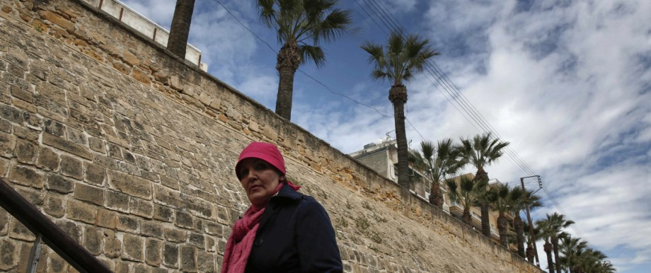 A woman walks up stairs in front of Venetian walls in Nicosia