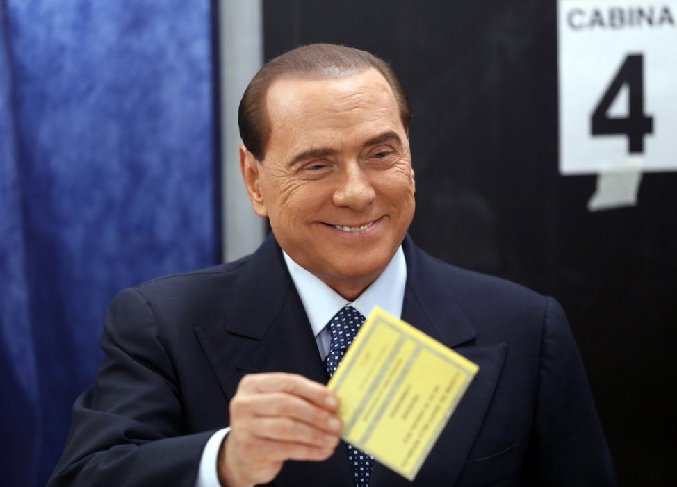 Former PM Berlusconi smiles as he casts his vote at the polling station in Milan