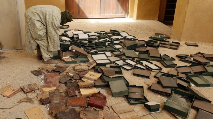 A museum guard sorts through burnt ancient manuscripts at the Ahmed Baba Institute in Timbuktu