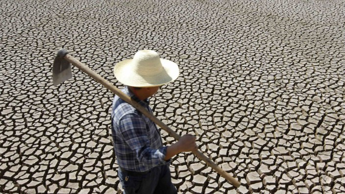 A farmer carrying a hoe walks past a dried-up pond in Shilin Yi Autonomous County of Kunming