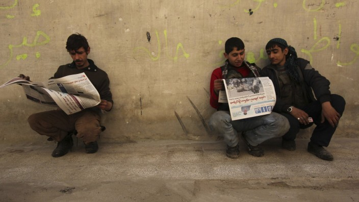 Residents read SHAAM News newspapers published by the Free Syrian Army, in Aleppo