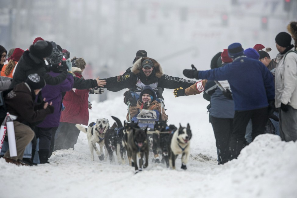 Musher Failor greets spectators as he races down 4th Avenue at the ceremonial start to the Iditarod dog sled race in downtown Anchorage, Alaska