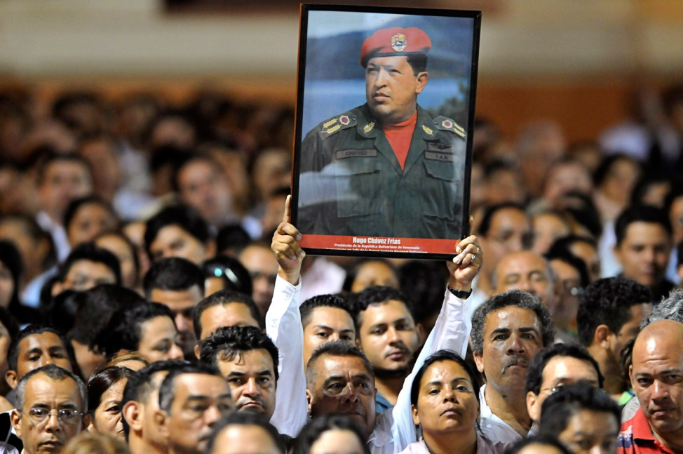 A Nicaraguan supporter of Venezuelan President Hugo Chavez holds a poster of him at the Revolution Square in Managua