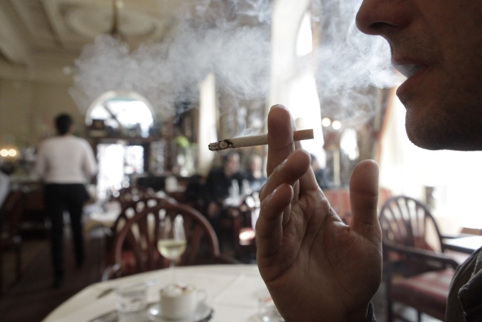 A customer smokes a cigarette in a cafe in Vienna