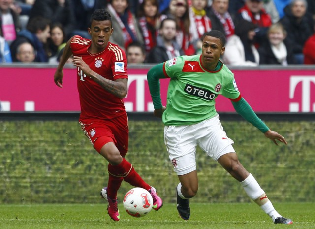 Bayern Munich's Gustavo is tackled by Duesseldorf's Bolly during German first division soccer match in Munich