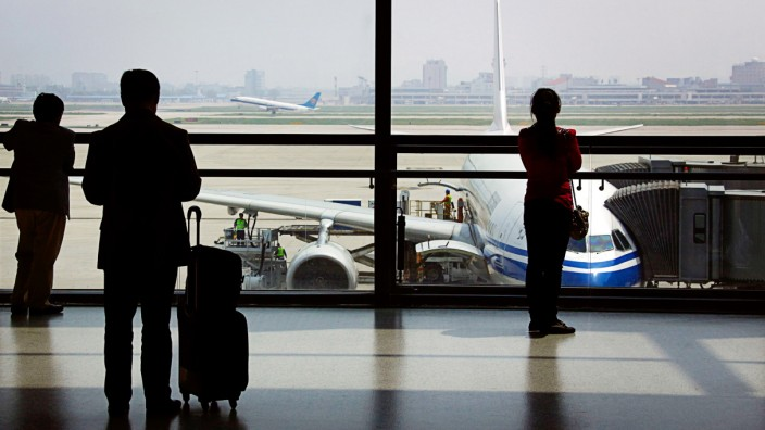 Passengers watch a China Southern Airlines plane take-off as they wait to board their plane at Shanghai's Hongqiao International Airport