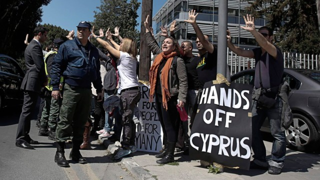 Demonstrators raise their arms in protest as Cypriot President Nicos Anastasiades's convoy drives to the parliament in Nicosia