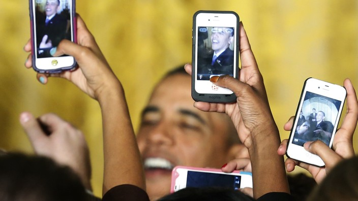 Attendees photograph U.S. President Obama with their phones at a Women's History Month reception in Washington