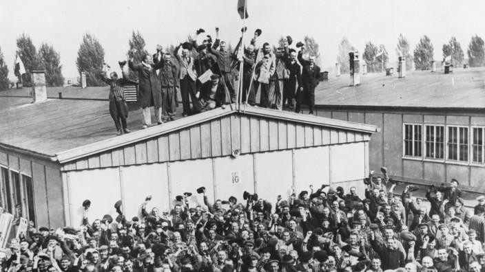 Jubelnde KZ-Häftlinge nach der Befreiung des KZ Dachau, 1945