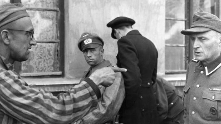 Häftling in KZ Dachau weist auf einen Wachmann, 1945 | concentration camp since 1945: Liberation -Dachau