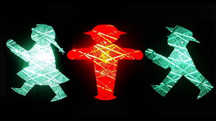 A combination of four pictures shows a pedestrian red and green crossing signal featuring a woman and an men in Zwickau