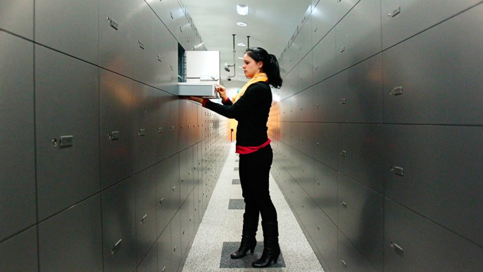 A woman takes a deposit box out of a compartment in the safe room of an Austrian bank in Vienna