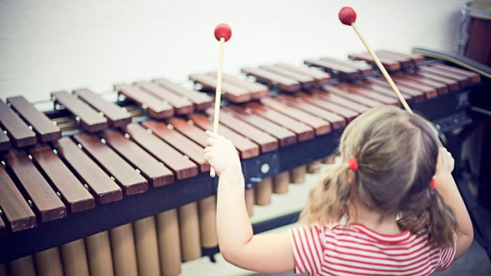 Musikalische Früherziehung: Kind spielt auf Xylophon Musik