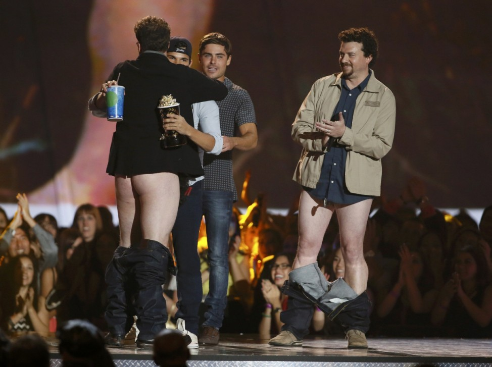 Presenter Rogen hugs the winner of the best shirtless performance, Taylor Lautner, as Efron and McBride watch at the 2013 MTV Movie Awards in Culver City