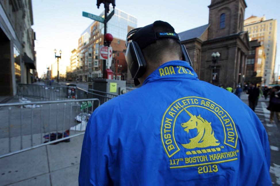 A man wearing a Boston Marathon runner's jacket is seen near the finish line of the race in Boston