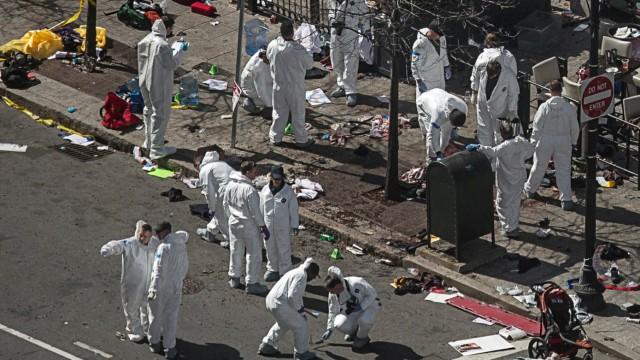Investigators survey the site of a bomb blast on Boylston Street a day after two explosions hit the Boston Marathon in Boston, Massachusetts