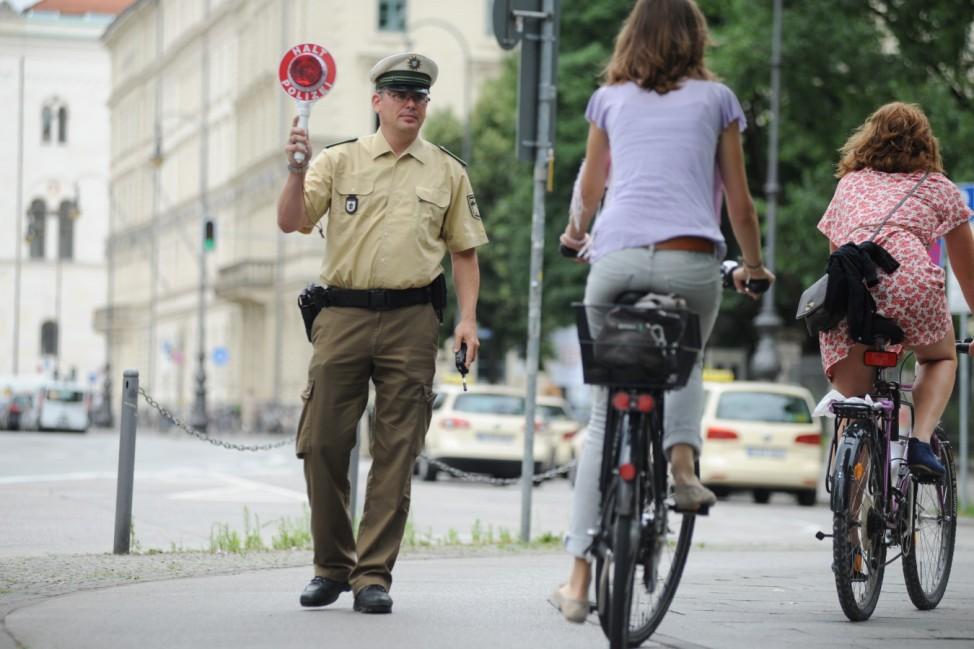 Polizist stoppt Fahrradfahrer in München.