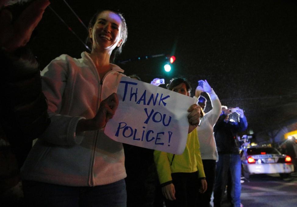 Members of the public cheer as police officers leave the scene where Dzhokhar Tsarnaev, suspect in Boston Marathon bombings, was taken into custody in Watertown