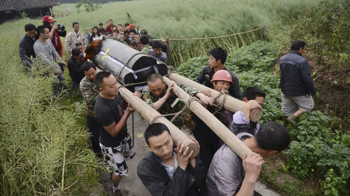 Villagers carry the coffin of a man killed in Saturday's earthquake, in Longmen