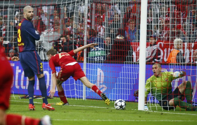 Bayern Munich's Thomas Muller celebrates next to Barcelona's Gerard Pique and goalkeeper Victor Valdes after scoring a goal during their Champions League semi-final first leg soccer match in Munich