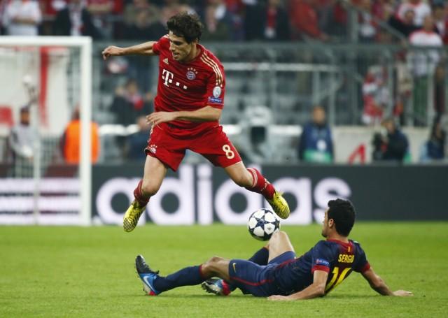 Bayern Munich's Javi Martinez jumps over Barcelona's Sergio Busquets during their Champions League semi-final first leg soccer match in Munich