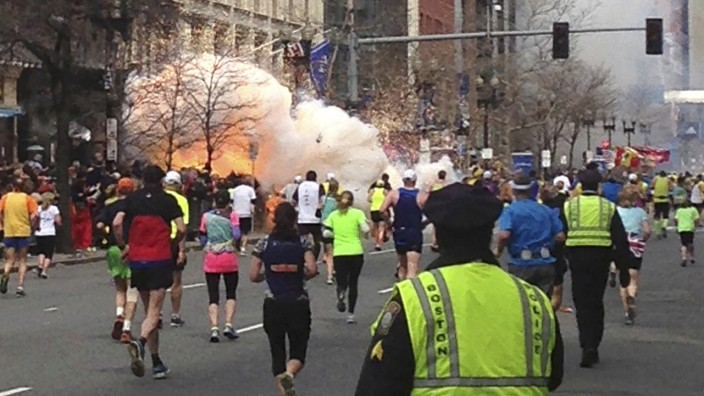 File picture of runners continuing to run towards the finish line as an explosion erupts at the finish line of the Boston Marathon