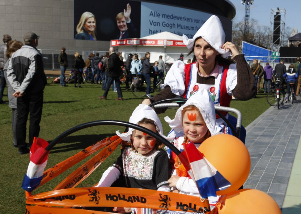Family passes a banner featuring Dutch Crown Prince Willem-Alexander and Crown Princess Maxima in Amsterdam