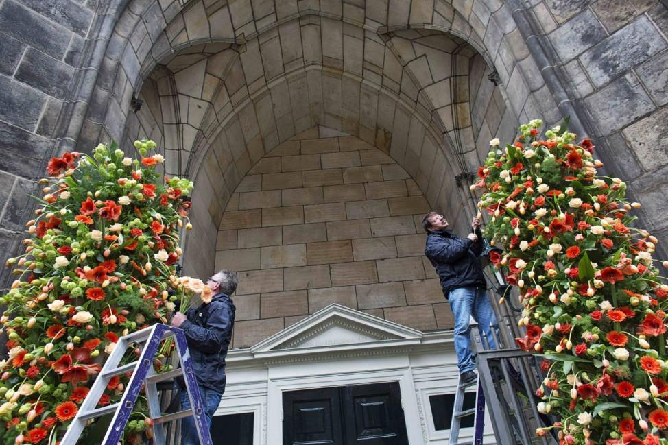 Florists arrange flowers outside the entrance of the Nieuwe Kerk church in Amsterdam