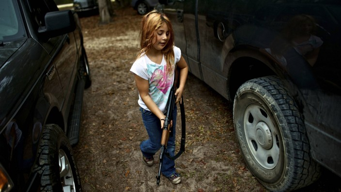 Brianna, 9, of the North Florida Survival Group carries an AK-47 rifle from the group leader's truck before heading out to conduct enemy contact drills during a field training exercise in Old Town