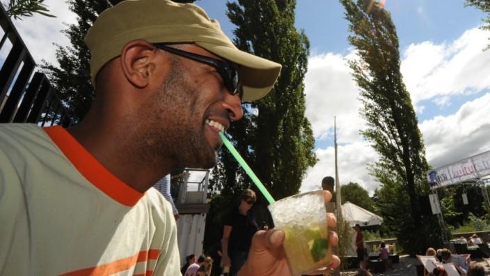 Ein Mann trinkt einen Cocktail aus einem Glas am Kulturstrand in München.