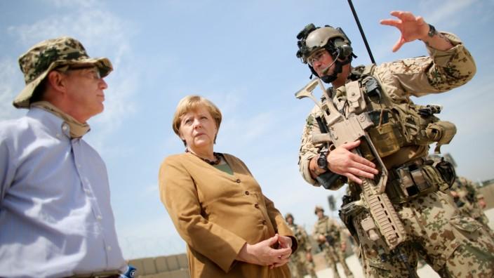 Deutschland und der Krieg: Kanzlerin Merkel und Verteidigungsminister de Mazière in Afghanistan