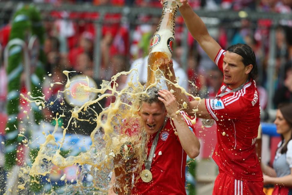 FC Bayern München ist Meister, Bastian Schweinsteiger wird von Daniel Van Buyten geduscht