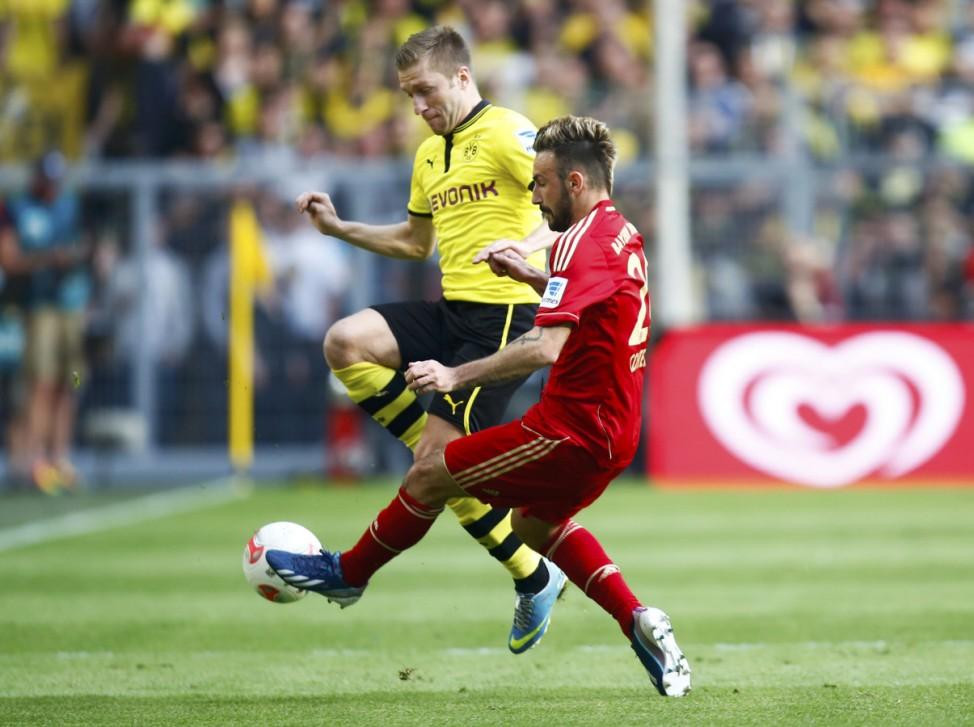 Bayern Munich's Contento fights for the ball with Borussia Dortmund's Blaszczykowski during their German first division Bundesliga soccer match in Dortmund