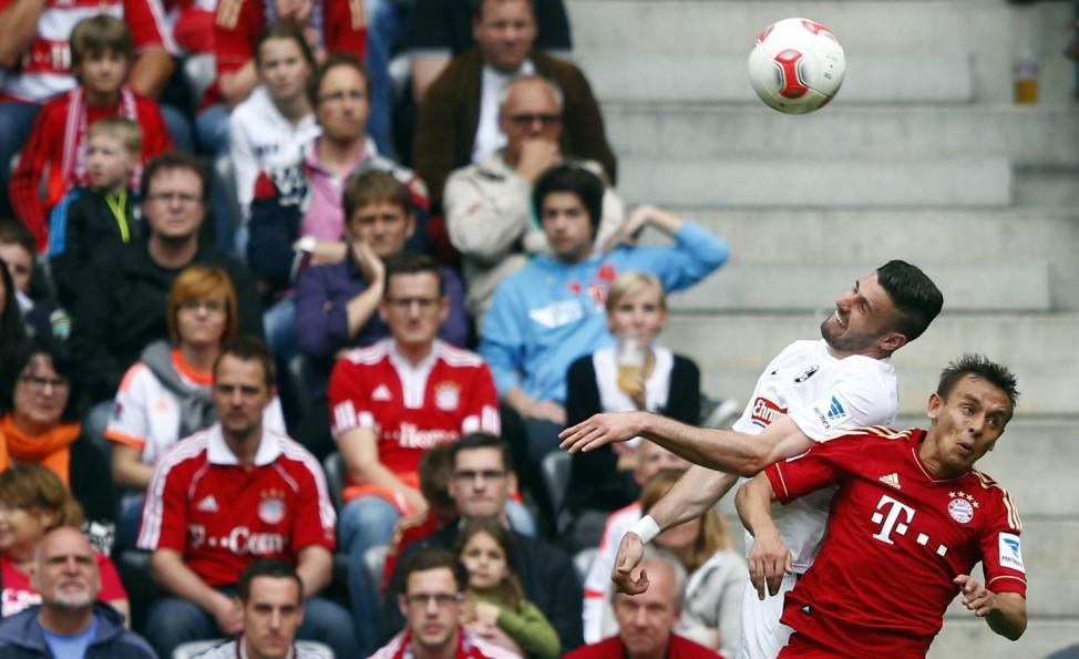 Munich's Rafinha challenges Freiburg's Caligiuri during their German Bundesliga first division soccer match in Munich