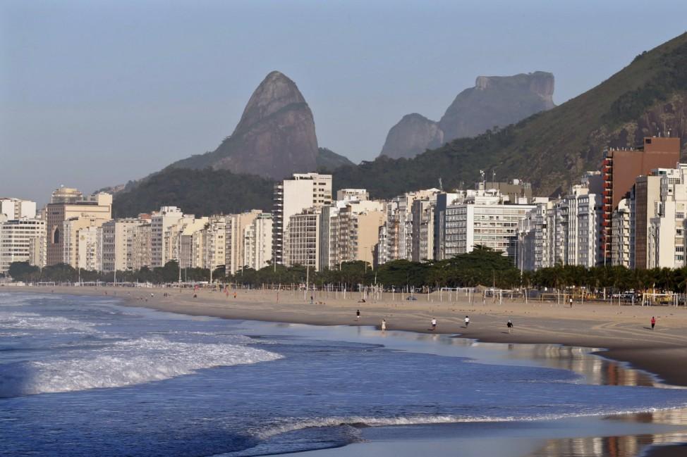 Beachgoers walk on Copacabana beach in Rio de Janeiro
