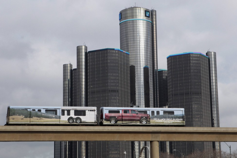 Public rail are covered with advertisement for GM pickup truck as they move past General Motors World Headquarters in Detroit