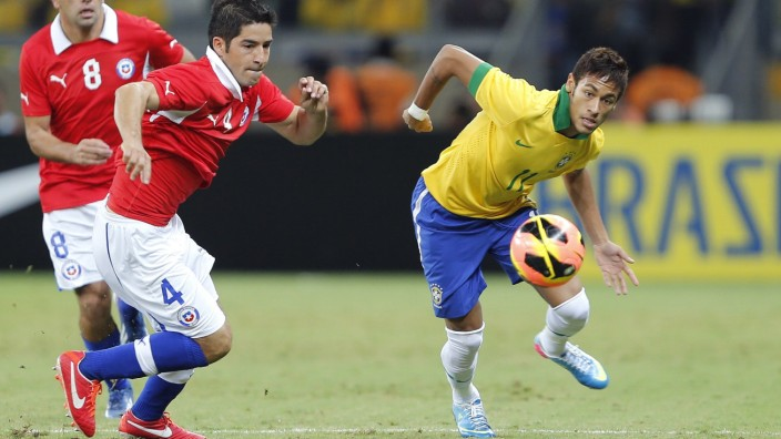 Brazil's Neymar races to the ball against Chile's Cristian Alvarez during their international friendly soccer match in Belo Horizonte