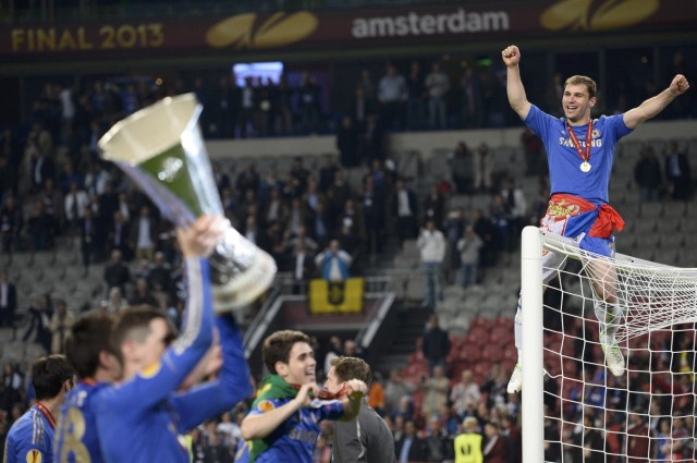 Chelsea's Frank Lampard holds the trophy as Branislav Ivanovic sits on a goalpost after they defeated Benfica in their Europa League final soccer match at the Amsterdam Arena